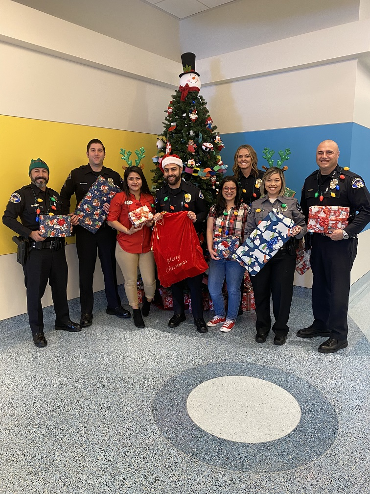 Police Officers and other participants holding presents in front of a Christmas tree