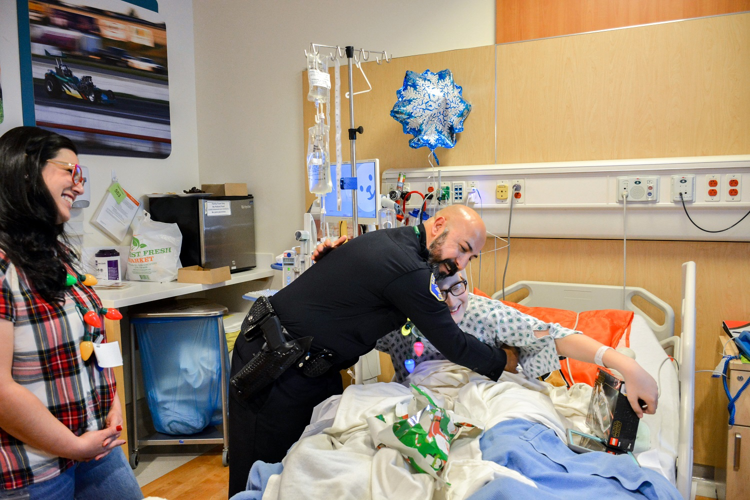 A police officer hugging a child in a hospital bed, both are smiling