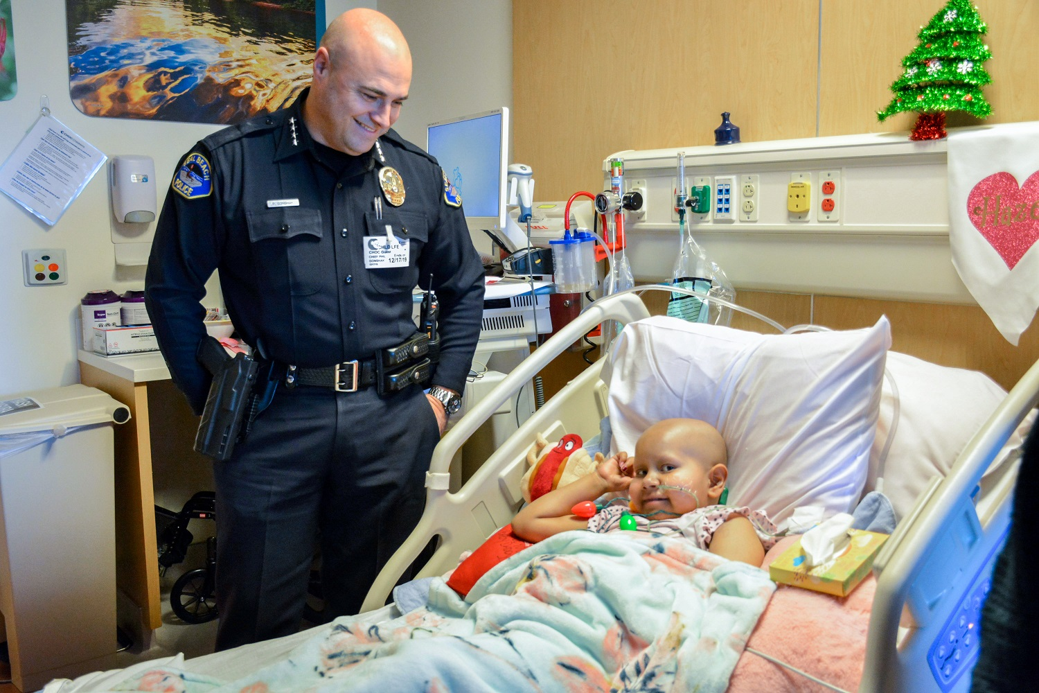 A police officer smiling at a child in a hospital room with holiday decorations; the child is wearing a holiday light necklace