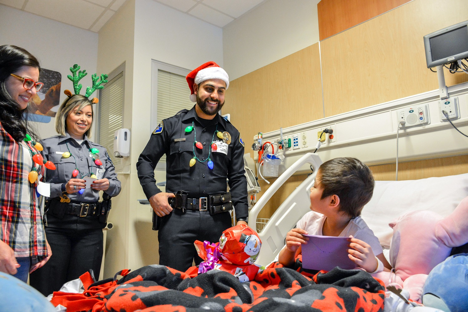 Police officers and a volunteer smile at a child opening a present in a hospital room